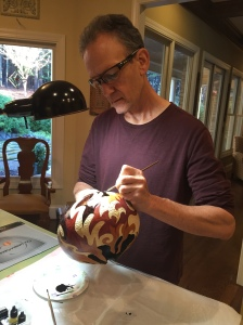 Martin staining a gourd he carved