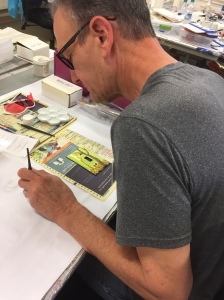 Martin paints a switch plate after enameling